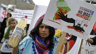 Kolombiyalı bir kadın, İsviçreli Glencore'un maden işletmesinden dolayı kirlenen suyunu gösteriyor