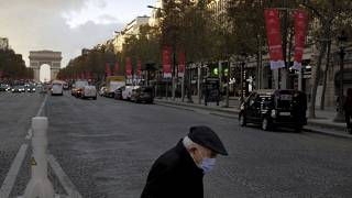 An elderly man wears a face mask as he walks on the Champs Elysee avenue, in Paris, Thursday, Nov. 19, 2020.