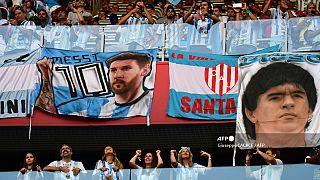 صورة من الارشيف- مشجعو الأرجنتين، ملصقات الأولى تحمل صورة  ليونيل ميسي والثانية صورة دييغو مارادونا