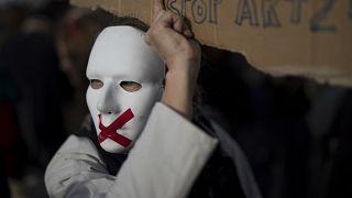"""متظاهر يرتدي قناعا ويحمل لافتة معترضا على المادة الـ24 من قانون """"الأمن الشامل""""، الذي ينص على حظر بث صور لعناصر الأمن والشرطة في فرنسا .مرسيليا"""