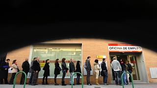 People line up to enter a government job center in Madrid,