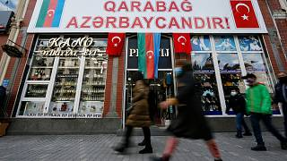 "People walk past a poster reading ""Karabakh is Azerbaijan"" in Ganja, Azerbaijan's second largest city, near the border with Armenia, Azerbaijan, Thursday, Nov. 26, 2020."