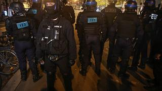 Police officers face demonstrators during a rally on the Place de La Republique, Tuesday, Nov.24, 2020 in Paris.