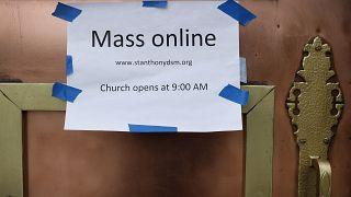 """على الباب الأمامي لكنيسة القديس أنتوني الكاثوليكية """" القداس على الإنترنت"""" في دي موين، آيوا الأمريكية"""