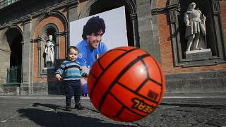 A child plays with a football in front of Naples' Royal Palace, which has a photo of Maradona hanging on it. Nov. 27, 2020.