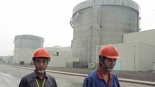 workers walk past a part of the Qinshan No. 2 Nuclear Power Plant, China's first self-designed and self-built national commercial nuclear power plant in Qinshan