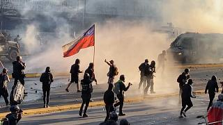 Protester holding Chilean flag march clashes with police