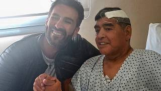 Argentine football legend Diego Maradona (R) shaking hands with his doctor Leopoldo Luque in Olivos, Buenos Aires province, Argentina.