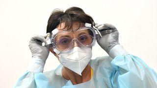 Koronavírus-teszthez öltözik védőruhába Bagdiné Bangócs Éva védőnő a Szolnok Városi Óvodák Hold utcai Tagintézményében 2020. november 27-én