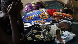 Kenya'nın batısında sıtma rahatsızlığına yakalanan çocuğuna bakan bir kadın (arşiv)