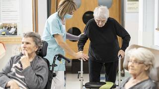 A man is helped before being tested with a PCR COVID test in a nursing home of Ammerschwihr, eastern France, Monday, Nov.9, 2020.