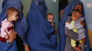Mothers hold their babies suffering from malnutrition as they wait at a UNICEF clinic in Jabal Saraj, north of Kabul, Afghanistan