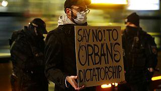 Egy tüntető Orbán-ellenes táblával Varsóban 2020. november 30-án