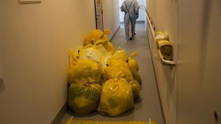 A medical worker passes by contaminated waste products in a hallway outside the intensive care ward for Covid-19 patients at the MontLegia CHC hospital in Liege.