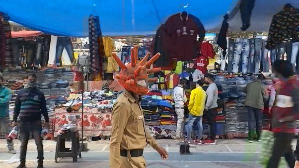 Policeman wearing a virus-shaped helmet walks around a busy market