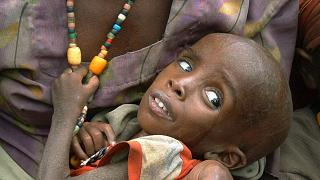 Etiyopya'da yardım bekleyen annesinin kucağında oturan bir çocuk (arşiv)