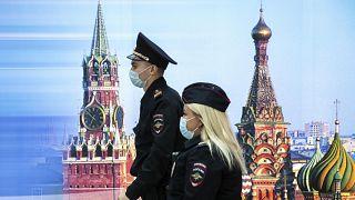 Сотрудники полиции идут мимо фотографии Спасской башни и Собора Василия Блаженного в аэропорту Шереметьево