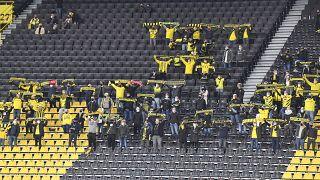 Anhänger von Borussia Dortmund umgeben von leeren Sitzen.
