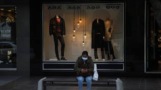 A woman wearing face mask sits on a bench at a main shopping street in capital Nicosia