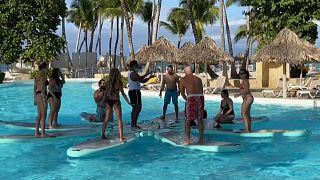 Un grupo de turistas hace ejercicios con un monitor en la piscina de un hotel de la República Dominicana