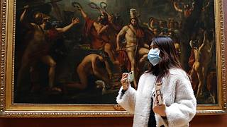 Masked tourist walks by an oil on canvas of 1814 entitled Leonidas at Thermopylae, by Jacques Louis David, at the Louvre Museum in Paris