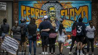 visitors make silent visits to organic memorial featuring a mural of George Floyd, near the spot where he died while in police custody, in Minneapolis.