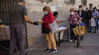 Una cola de personas aguarda para recoger alimentos donados por voluntarios y miembros de una congregación religiosa en Madrid