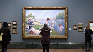 Visitors looking at a Georges Seurat painting