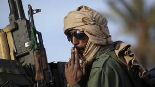 a pro-Gadhafi soldier smoke a cigarette on the top of a tank on the main square of Zawiya, Libya, 50 kms (30 miles) west of Tripoli, Friday, March 11, 2011