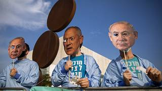 Israeli demonstrators hold masks depicting Benjamin Netanyahu and Benny Gantz during a protest against a vote to dissolve the Knesset.