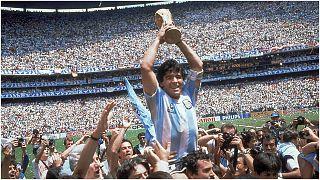 مارادونا يحمل كأس العالم التي فاز بها منتخبه الأرجنتين عام 1986