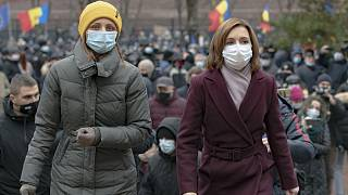 Moldova's president elect Maia Sandu, right, walks away after addressing protesters outside the parliament building in Chisinau, Moldova, Thursday, December 3, 2020.