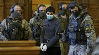 Hassan F., a Syrian man accused of mass executions, terrorist acts and crimes against humanity is escorted by Hungarian police special unit officers as he arrives in the court