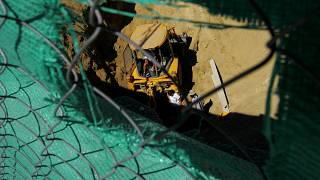 Experts search a well for remains of missing persons with the help of a bulldozer in the divided capital Nicosia