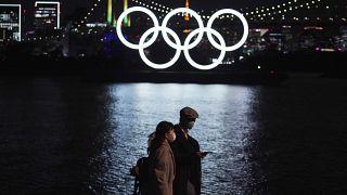 رجل وامرأة يمشيان حذو شعار الأولمبياد العائم في طوكيو. 2020/12/01