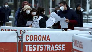 People line up a corona test street for a mass Covid-19 testing in Vienna, Austria