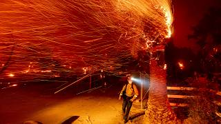 A firefighter runs past a burning tree while battling the Bond Fire in the Silverado community of Orange County, California, USA. December 3, 2020