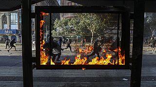 Manifestantes correm em frente a uma estação de autocarros em chamas