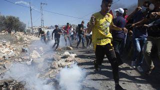 فلسطينيون يفرون من الغاز المسيل للدموع خلال تظاهرة في الضفة الغربية المحتلة