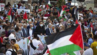 فلسطينيون يلوحون بالأعلام احتجاجاً على تطبيع العلاقات بين الإمارات العربية المتحدة والبحرين مع إسرائيل، رام الله بالضفة الغربية