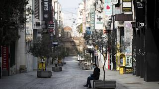 A man wearing a face mask and plastic gloves to protect from coronavirus sits in the empty Ermou Street
