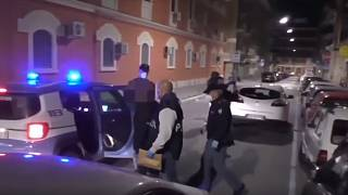 A suspect is led away by police