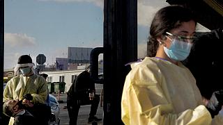 A health worker, left is reflected in a door of a building as he carries out a rapid coronavirus test, on a main avenue in Strovolos in Nicosia