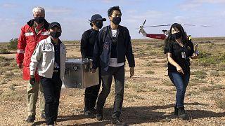Miembros del Organismo de Exploración Aeroespacial de Japón cargan una caja que contiene muestras de asteroides que recuperaron en el sur de Australia tras su aterrizaje.