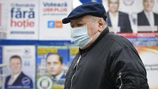 Un anciano con mascarilla camina junto a varios carteles electorales en Bucarest, la capital de Rumanía.
