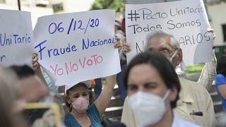 متظاهرون يرفعون لافتات مؤيدة لمقاطعة الانتخابات التشريعية المقبلة أثناء تجمعهم لاستقبال زعيم المعارضة السياسية الفنزويلي فريدي جيفارا