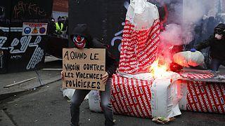 """متظاهر يحمل ملصق كتب عليه """"لقاح ضد عنف الشرطة"""" أمام حاجز خلال مظاهرة يوم السبت 5 ديسمبر 2020 في باريس"""