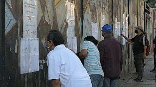 Varios votantes buscan su mesa a su llegada a los centros electorales