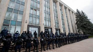 Riot police forces stand guard in front of the government building