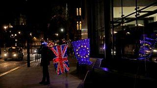 Egy brexitellenes tüntető kivilágított brit és EU-s zászlóval Londonban